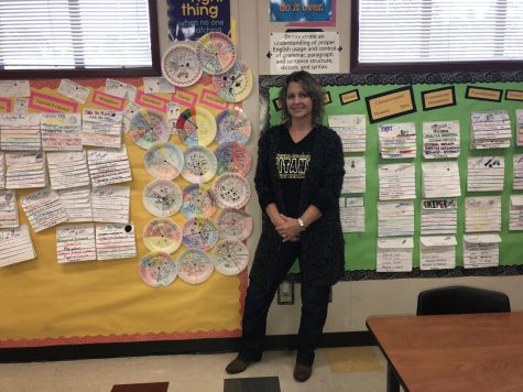 Kimberly Hughes proudly standing in front of her students excellent work wall.