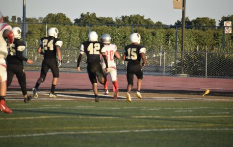 Multiple Titans try to chase down a Trojan running back.